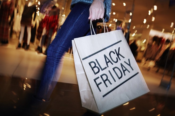 Woman carrying shopping bag labeled Black Friday through shopping mall.