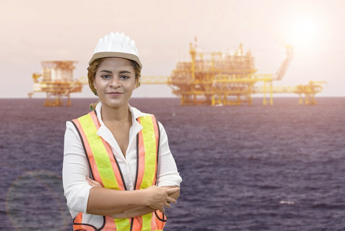 A worker with offshore oil rigs in the background.