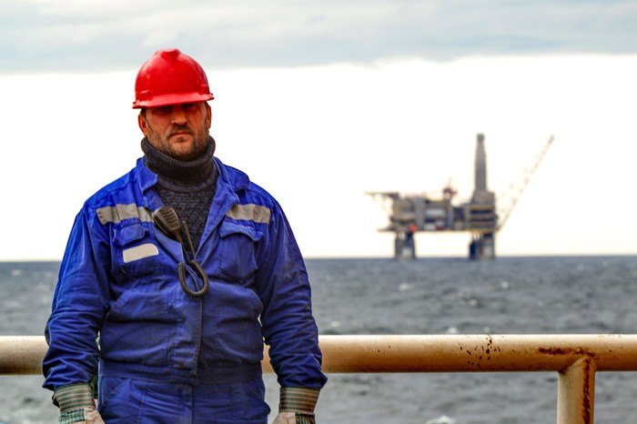 A man in a blue work suit with an oil rig in the background.