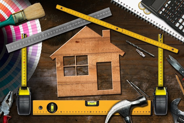 A wooden house cutout surrounded by various home improvement tools.