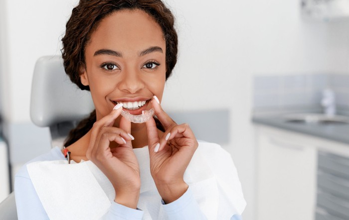 A smiling woman holds a translucent teeth straightener device.
