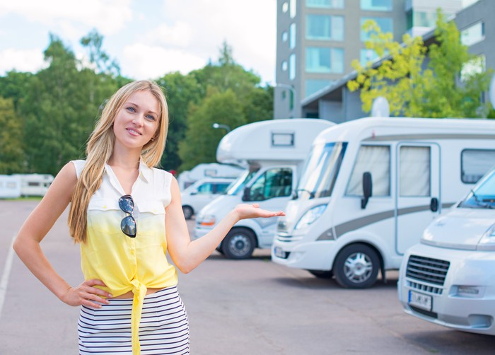 A perky-looking saleswoman in a yellow shirt showing RVs at a dealership.
