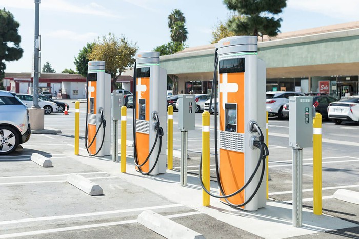 A row of three ChargePoint electric-vehicle chargers, with the company's characteristic orange branding.