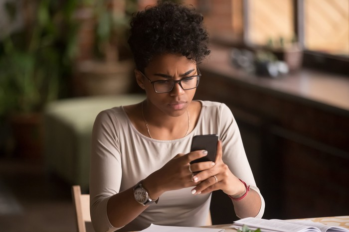 Upset woman looking at phone screen