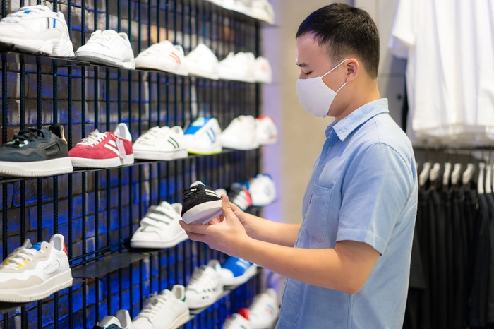 A man wears a cloth mask while considering a display of athletic shoes.