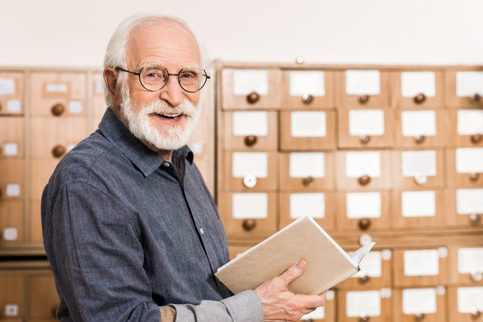 Smiling older person with book in hand.