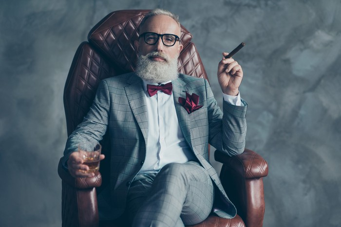 A man with a white beard in a suit and bow tie drinks a cigar in one hand in the other.