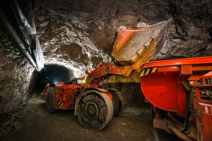 An excavator operating in an underground precious-metal mine.
