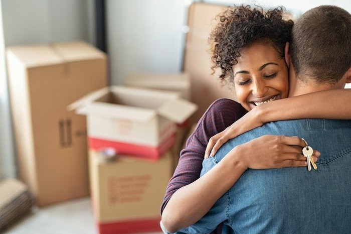 Couple embracing while holding house keys and moving boxes in the background.