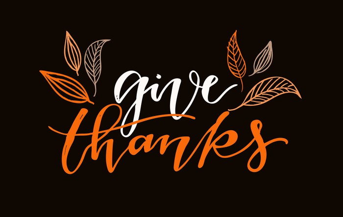 The words give thanks with leaves on a black background