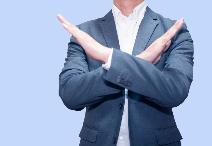 Photo of a businessman crossing his arms in a firm No gesture.