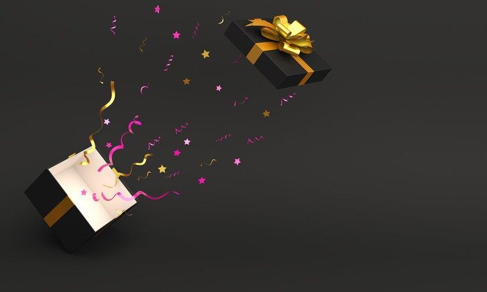 A gift box wrapped in golden ribbon launches off the top of a cube, leaving behind a trail of decorative items.