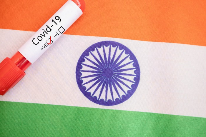 Vial labeled COVID-19 on top of an Indian flag