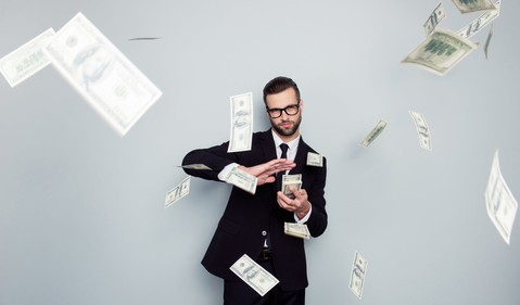 Man in business suit and glasses scattering $100 bills