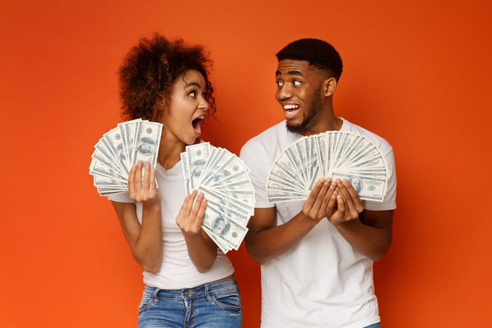 Stock photo of couple holdings cash bucks.