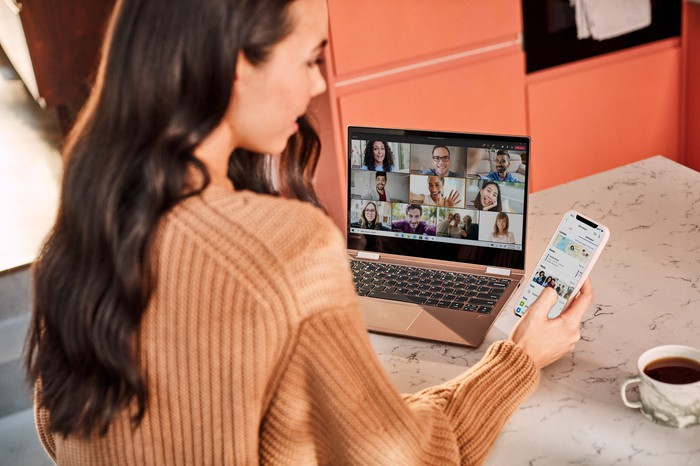 A woman uses Microsoft Teams on her phone and laptop.