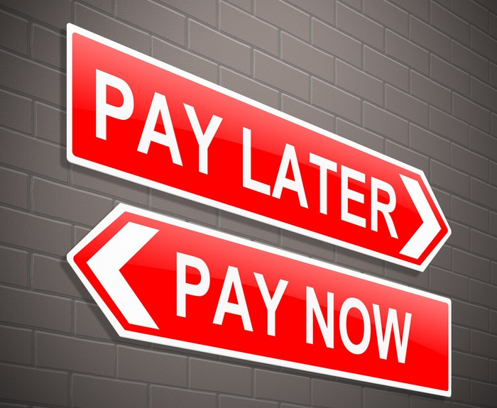 2 signs on a wall that say pay later and pay now
