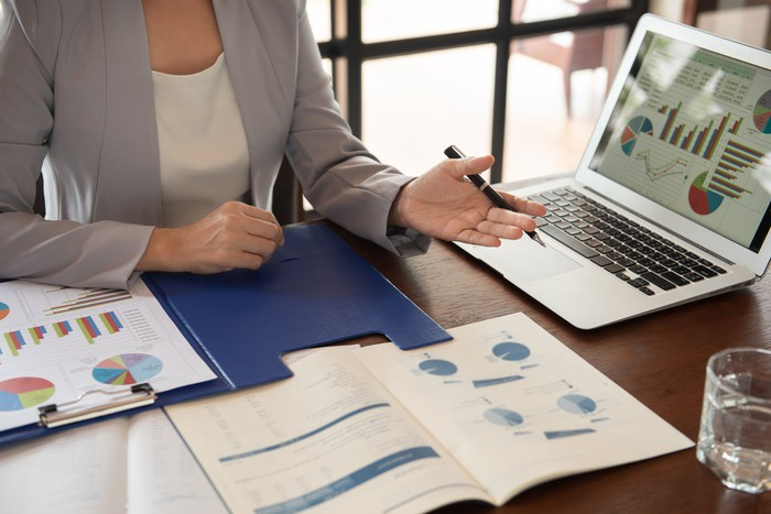 Woman at desk with laptop and documents with graphs in front of her