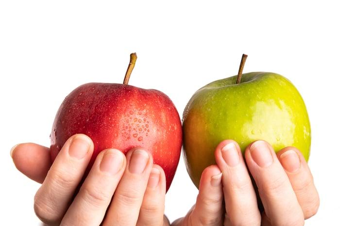 Apel merah diangkat kontras dengan apel hijau.