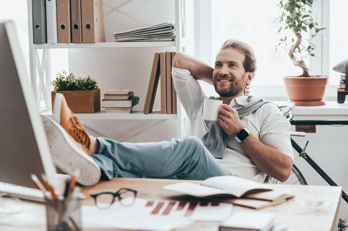 Seorang pria santai minum kopi sambil berbaring di kursi dan dengan kaki di atas meja.
