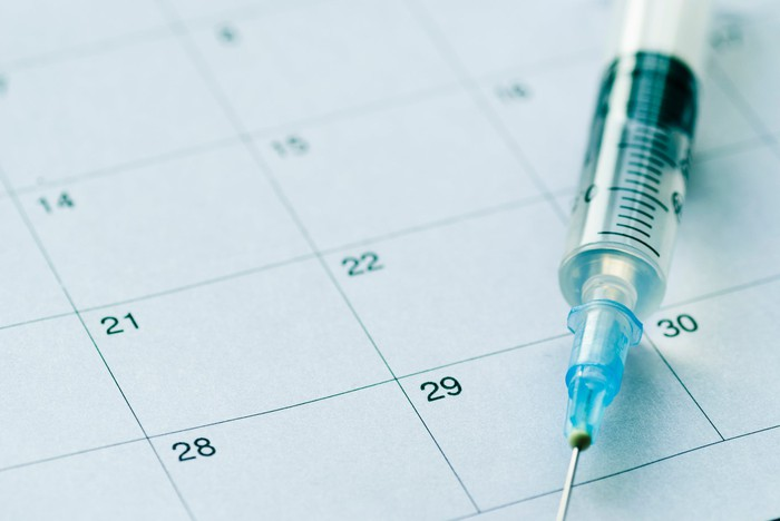 Syringe with needle on top of a calendar