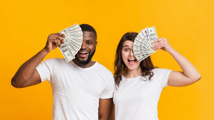 Young man and woman in white tee shirts holding cash in front of their faces.