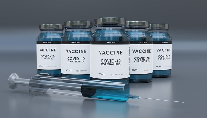 Syringe with vials labeled COVID-19 vaccine