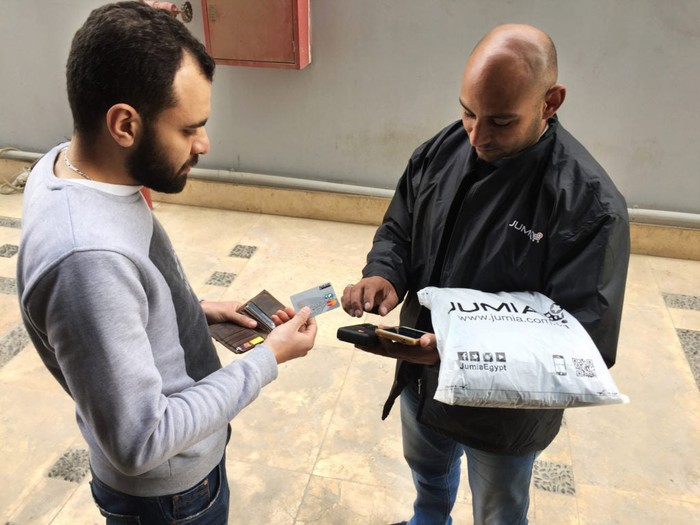 Man hands another man credit card to pay for a Jumia package