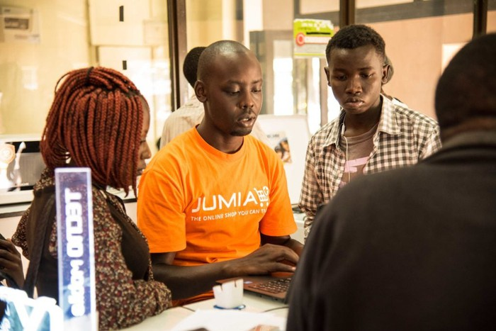 People from Jumia are looking at a computer screen inside a building.