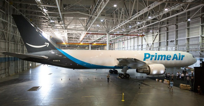 An airplane in a hangar with Prime Air painted on it.
