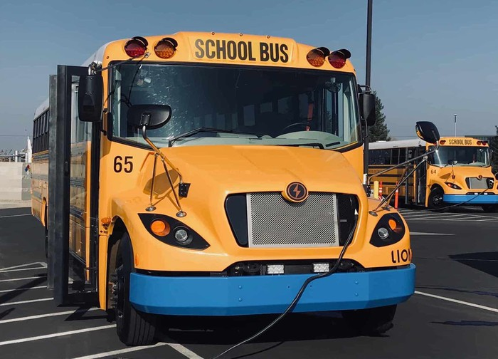 A Lion Electric school bus, parked with a recharging cable attached.