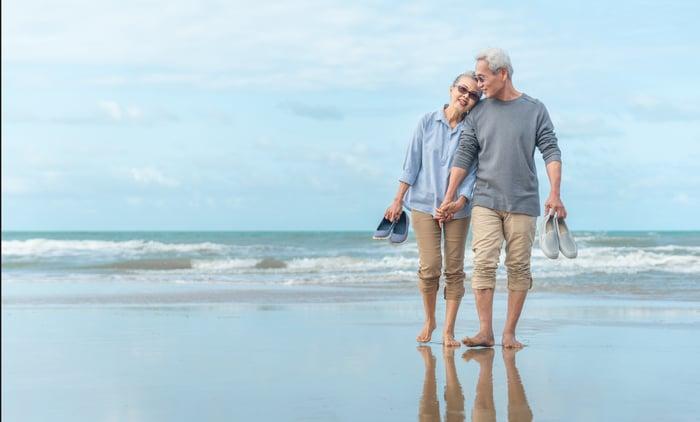 Older couple walking barefoot on the beach.