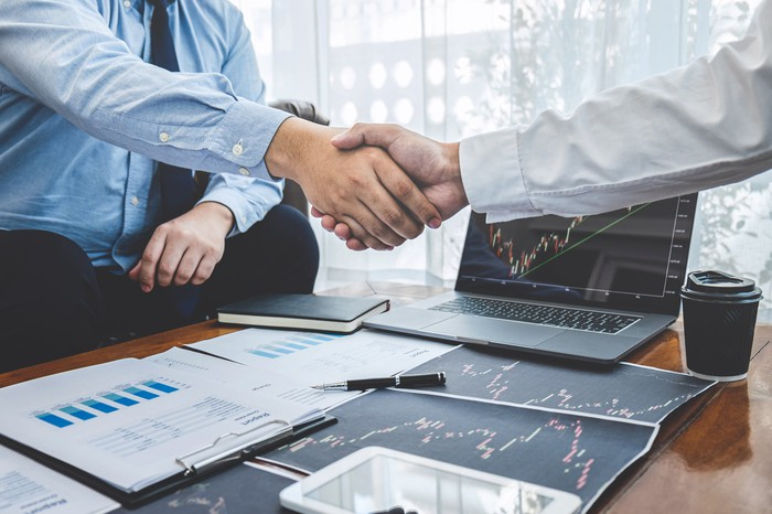 Two businesspeople shaking hands over a desk in an office.