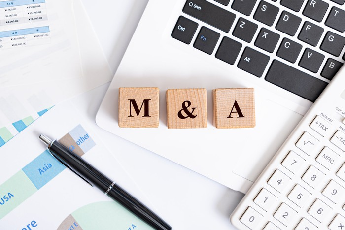 picture of blocks spelling M&A, a pen and computer keyboards