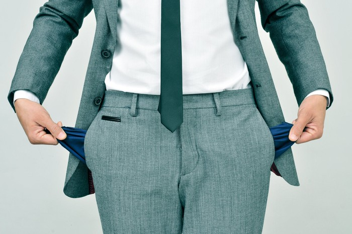 Man in suit pulling his pockets out to show that they're empty.