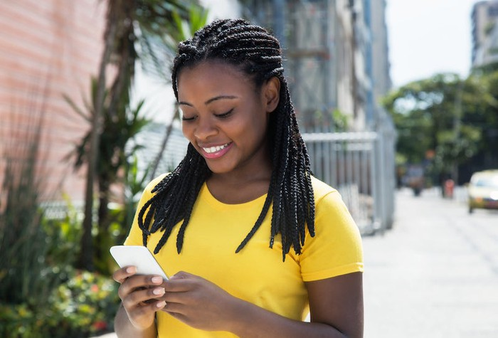 A woman smiles while looking at a smartphone.