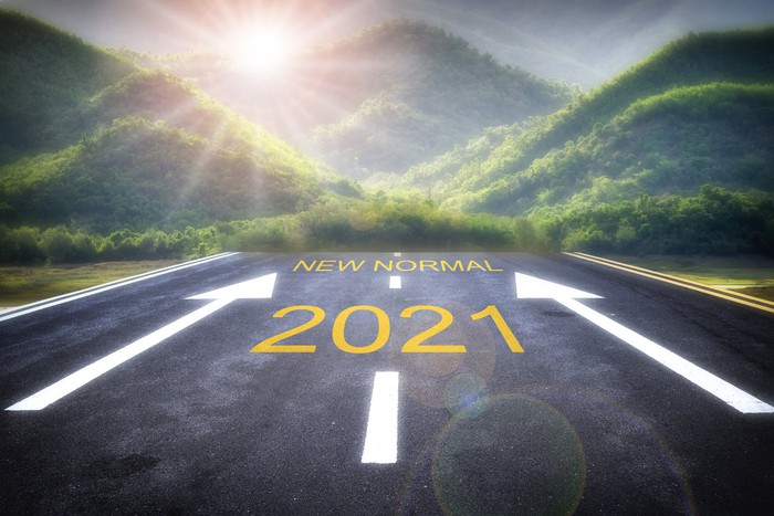 road with 2021 and arrows pointing to words new normal heading into green mountains