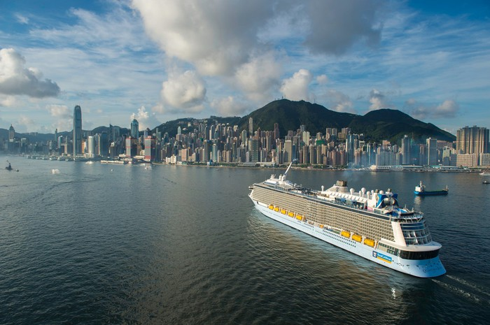 Royal Caribbean's Quantum of the Seas sailing off Hong Kong under a cumulus-dotted sky.