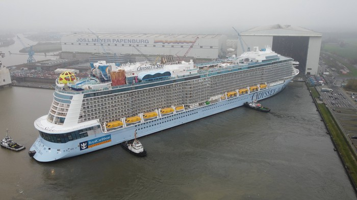 Odyssey of the Seas being moved by tugboats at its German shipyard.