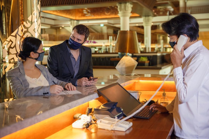 Two people, wearing masks, checking into a hotel while being helped by the hotel clerk, wearing a mask.