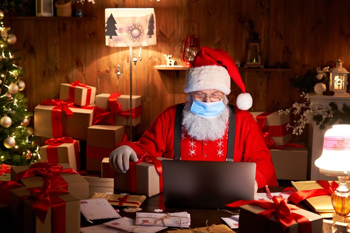 Santa Claus wearing a face covering typing on a laptop surrounded by packages.