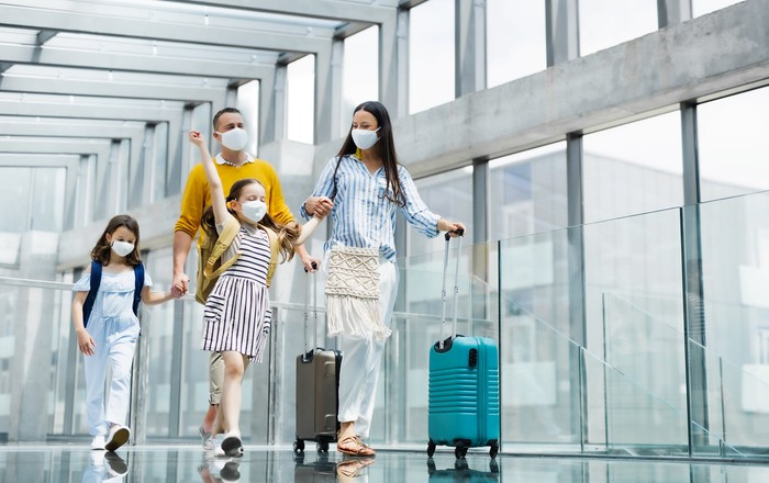 A family of four wears face masks and tows luggage through an airport.