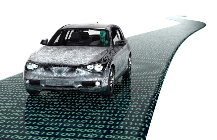 Rendering of a passenger car driving on a road covered in green ones and zeroes on a shiny black surface.