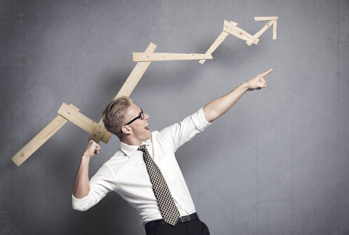 Man smiling and pointing upwards in front of wooden planks made into an arrow that's also pointing upward.