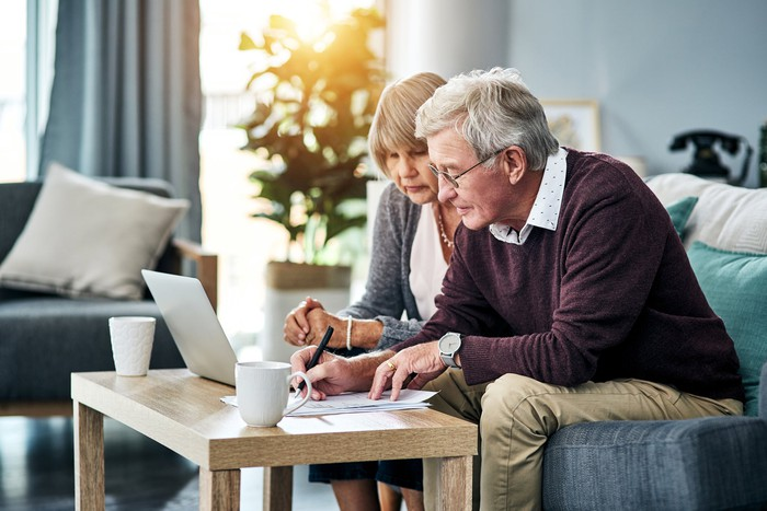 Senior couple sitting on a couch looking at documents and a laptop