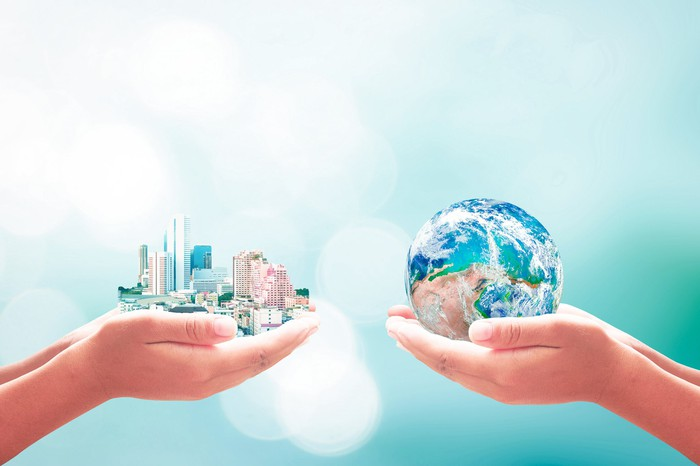 Close up of two hands, one holding a globe and the other holding a cityscape.