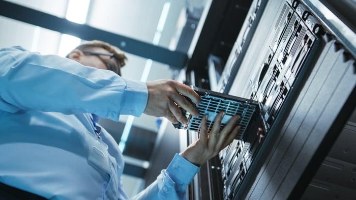 Un ingénieur plaçant un disque dur dans une tour de serveurs de centre de données.