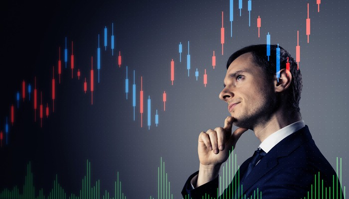 A pensive businessman with a stock chart going up and to the right overlaid.