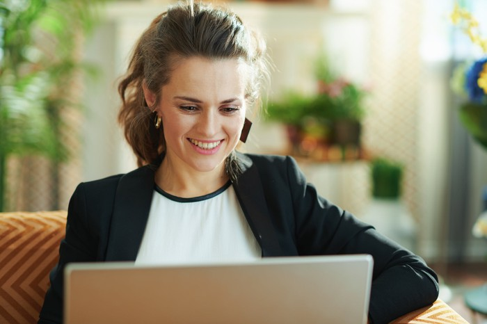 An investor smiles as she researches stocks on her laptop.