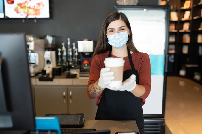 Barista wearing face mask, serving a beverage in a paper cup.